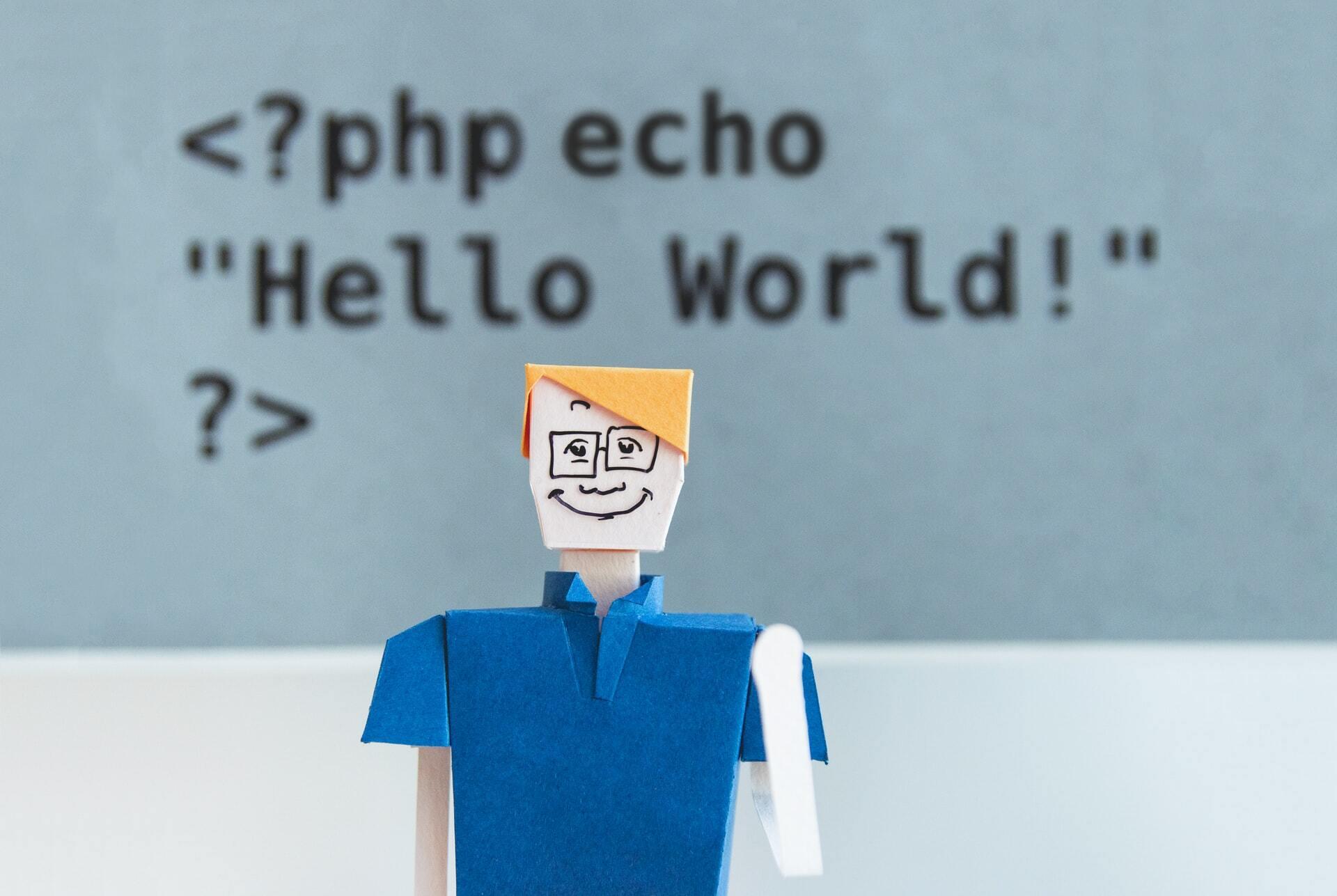 Zdjęcie przedstawia ludzika z papieru (origami), za którym widnieje napis Hello World.