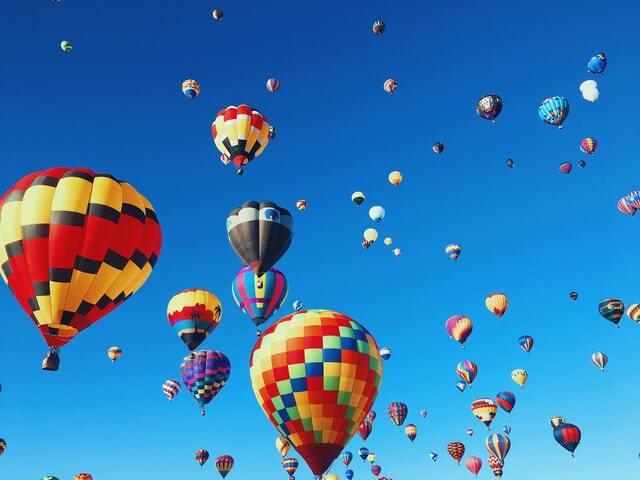 Na tle błękitnego nieba widać wiele kolorowych balonów.