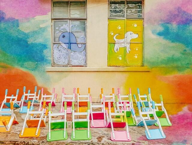 Na zdjęciu widać kolorową ścianę, a na kolorowej podłodze porozrzucane są kolorowe krzesełka.