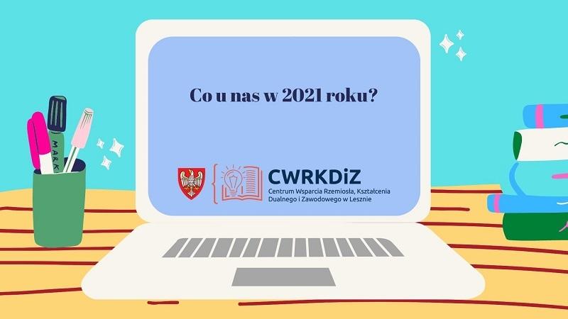 """Grafika wektorowa przedstawiająca biały komputer na brązowym stole. Po lewej stronie w kubeczku znajdują się długopisy i markery, a po prawej książki. Na ekranie komputera napis """"Co u nas w 2021 roku?"""" i logo CWRKDiZ w Lesznie."""