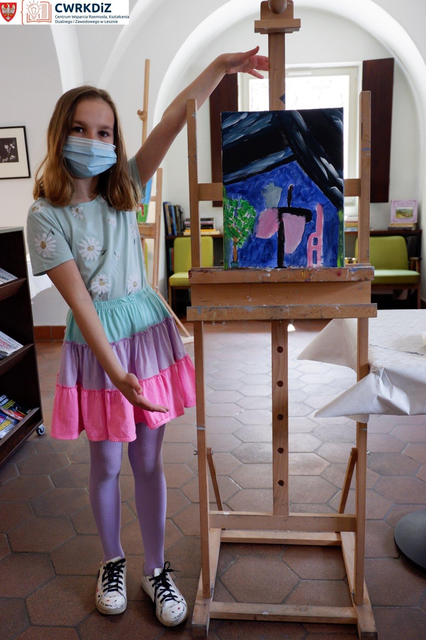 Dziewczynka stoi obok sztalugi i prezentuje postawiony na niej wykonany przez siebie obraz.
